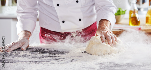 Man sliding dough along table to pick up flour - 226990471