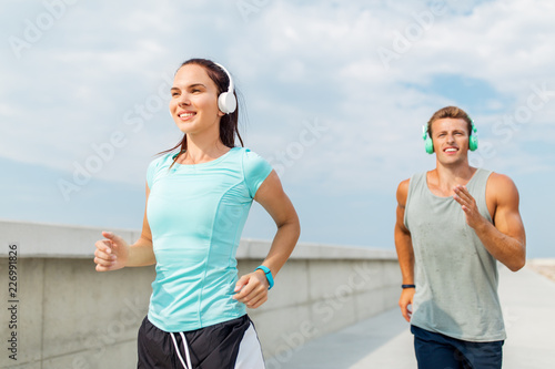Poster sport, people and technology concept - happy couple with headphones and fitness trackers running outdoors