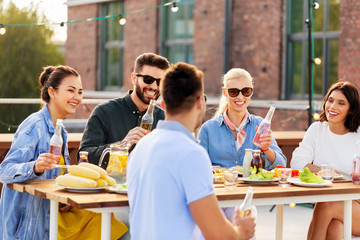 leisure and people concept - happy friends with drinks at rooftop party
