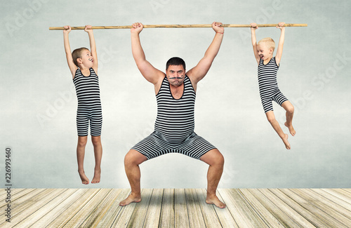 Leinwandbild Motiv Family of strongman. The father of two sons in vintage costume of athletes perform strength exercises. Family look.