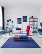 Leinwanddruck Bild - Posters on white wall above couch with pink blanket in flat interior with table on blue carpet. Real photo