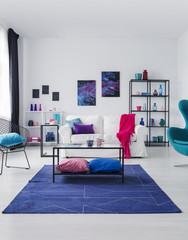 Posters on white wall above couch with pink blanket in flat interior with table on blue carpet. Real photo