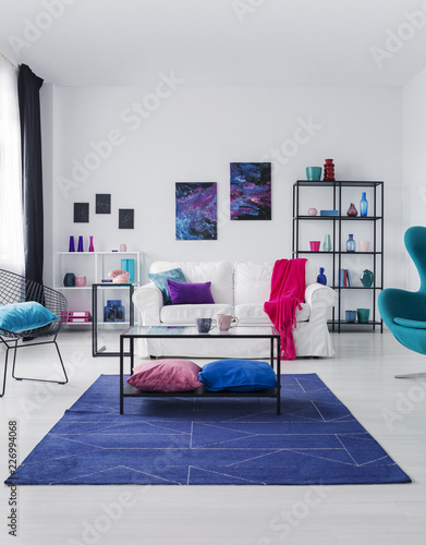 Leinwanddruck Bild Posters on white wall above couch with pink blanket in flat interior with table on blue carpet. Real photo
