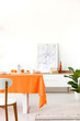 Quadro Plant and poster on cabinet in white dining room interior with chair at table with orange cloth. Real photo