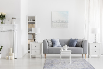 White table on carpet in front of grey settee in apartment interior with painting and lamp. Real photo