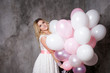 Charming young blonde in a white dress with pink balloons, at the party.