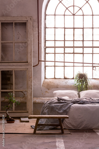 Foto Murales Real photo of a wabi sabi bedroom interior with a big, old window and bed