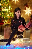 Beautiful happy young woman with christmas lights - 227008059