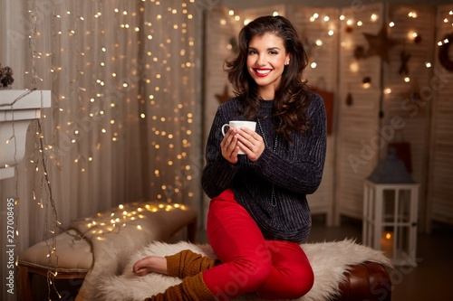 Leinwanddruck Bild Young woman at fireplace with hot drink