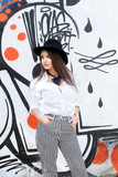 Beautiful female model wearing striped pants, a white shirt and black bow and hat looking a side near a graffiti wall