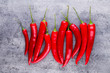 Leinwandbild Motiv Chili cayenne pepper on grey background.