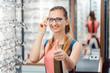 Leinwandbild Motiv Frau empfiehlt neue Brillen zu kaufen