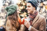 Frau und Mann trinken Glühwein auf Weihnachtsmarkt