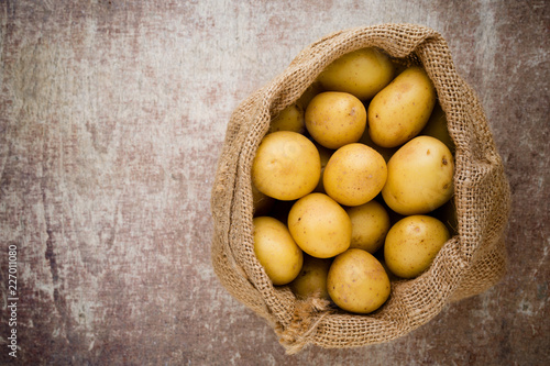 Poster Sack of fresh raw potatoes on wooden background, top view.