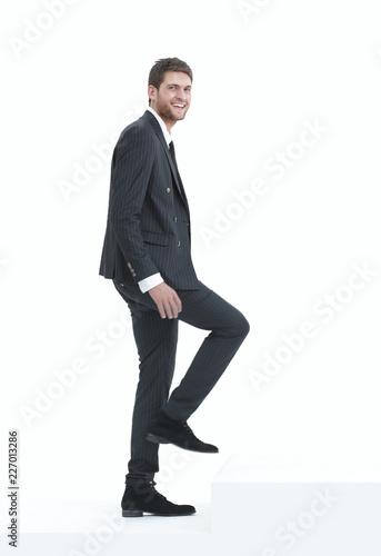 Leinwandbild Motiv full growth.businessman taking a step forward.isolated on white.