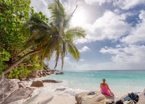 Foto Murales Young woman enjoying the beach at Seychelles Praslin beach paradise holiday vacation. Travel to Seychelles for beautiful sea and white beaches in Indian Ocean, Africa. Rocks on the beach.