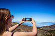 Young woman taking a photo with her phone of amazing mountains landscape on Tenerife, Canary islands, Spain. Travel concept