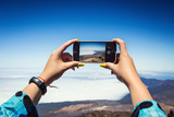 Young woman taking a photo with her phone of amazing mountains landscape on Tenerife, Canary islands, Spain. Travel concept - 227026449
