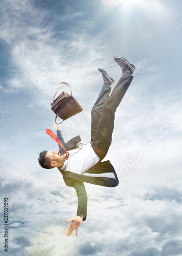 Leinwandbild Motiv The frightened businessman in suit falling down and screaming against blue sky background. concept of failure