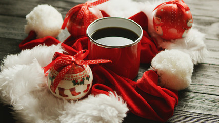 Closeup shot of nice Christmas hats and lovely baubles lying around mug of aromatic hot beverage on timber tabletop