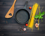 The thin spaghetti on black wooden background. Yellow italian pasta with ingredients. Italian food and menu concept. - 227066224