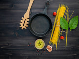 The thin spaghetti on black wooden background. Yellow italian pasta with ingredients. Italian food and menu concept. - 227066241