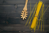 The thin spaghetti on black wooden background. Yellow italian pasta with copy space . Italian food and menu concept. - 227066484