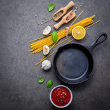 The thin spaghetti on dark stone background. Yellow italian pasta with ingredients. Italian food and menu concept. - 227067070