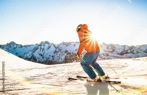 Leinwandbild Motiv Professional skier athlete skiing at sunset on top of french alps ski resort - Winter vacation and sport concept with adventure guy on mountain top riding down the slope - Warm bright sunshine filter
