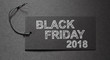 Black Friday 2018 text on a black tag on black paper background