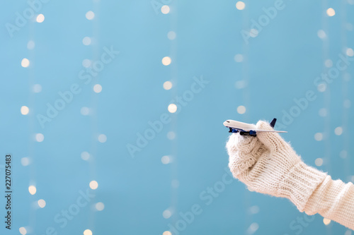 Woman holding a toy airplane on a shiny light blue background