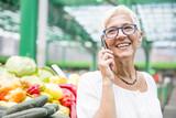Senior woman on market using mobile phone - 227078491