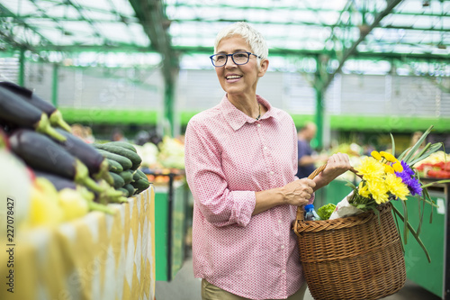 Foto Murales Senior woman holding basket with bouquet of flowers on market