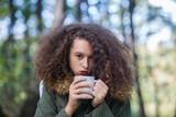 Curly hair teen girl holding mug in the park