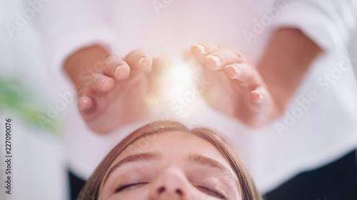 Leinwandbild Motiv Close Up Of A Relaxed Young Woman Having Reiki Healing Treatment