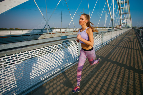 Foto Murales Young sports woman  jogging on the bridge