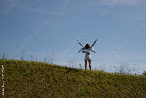 woman standing on top of the hill in warm sunny day - 227103867