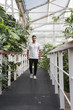 young man walking down a catwalk surrounded by plants