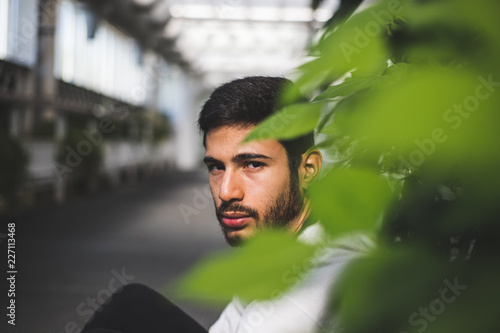 Foto Murales portrait of young man among green leaves