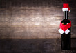 Wine bottle decarated with santa claus hat and scarf on wooden background
