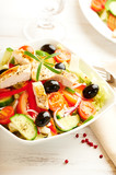 Chicken salad with cherry tomatoes, black olives, cucumber, red onion, red pepper, lettuce and fresh rosemary. Home made food Concept for a tasty and healthy meal Bright wooden background. Copy space  - 227125243