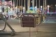 Quadro Carousel in the illuminated amusement park in the evening.