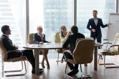 Leinwanddruck Bild Male employee give flipchart presentation to smiling colleagues at negotiations, man present project or idea to happy coworkers at briefing, workers laugh at office meeting, having casual talk