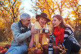 Senior parents drinking tea in autumn forest with their daughter. Family values. Having picnic