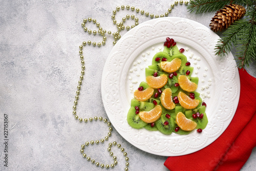 Edible christmas tree from kiwi and tangerine slices.Top view with copy space. - 227153067
