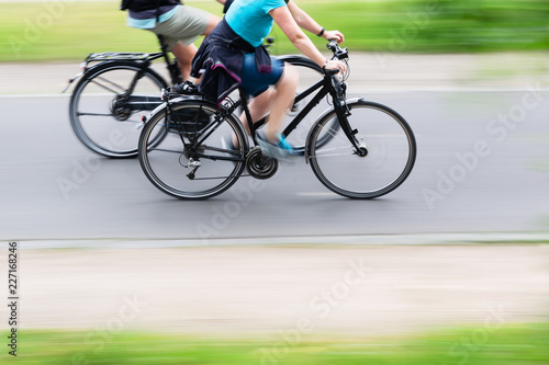 two bicycle riders on a cycle path in motion blur