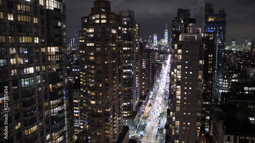 A long shot high angle time lapse view of traffic on 6th Avenue in Manhattan on a early Autumn night. The Freedom Tower is seen in the distance.
