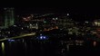 Aerial shot panning from right to left showcasing a few buildings in Downtown Jacksonville at night.