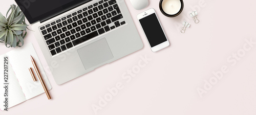 Leinwandbild Motiv modern header / hero image or banner with laptop computer, smartphone, air plant, open notebook and feminine accessories on a bright blush background, home office scene, flat lay / top view