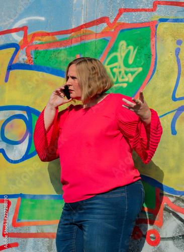 Posing von einem Model in rote Bluse vor einer Graffiti Wand
